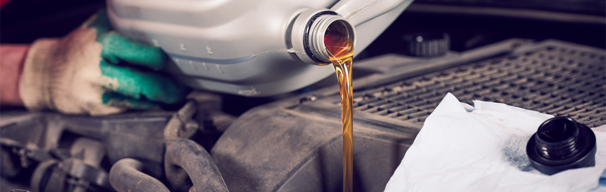 Mechanic topping up oil levels on a vehicle - Car Servicing Heanor